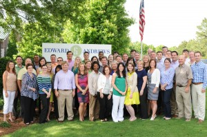 The Edward Andrews team gathers around their new corporate sign, the first time the public has seen the new brand.