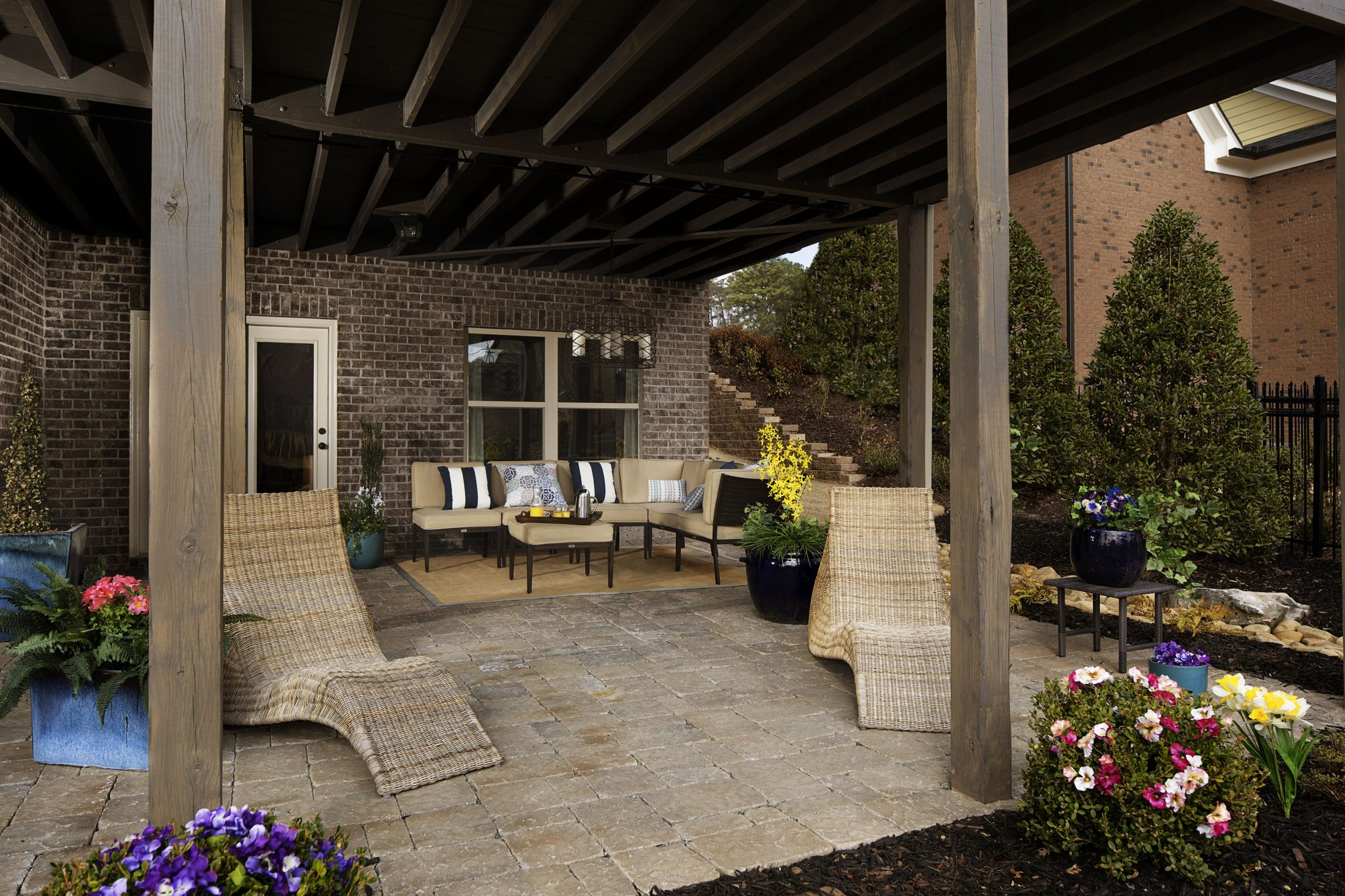 An outdoor oasis at Mabry Manor created with stone pavers, elegant lighting  and cozy seating